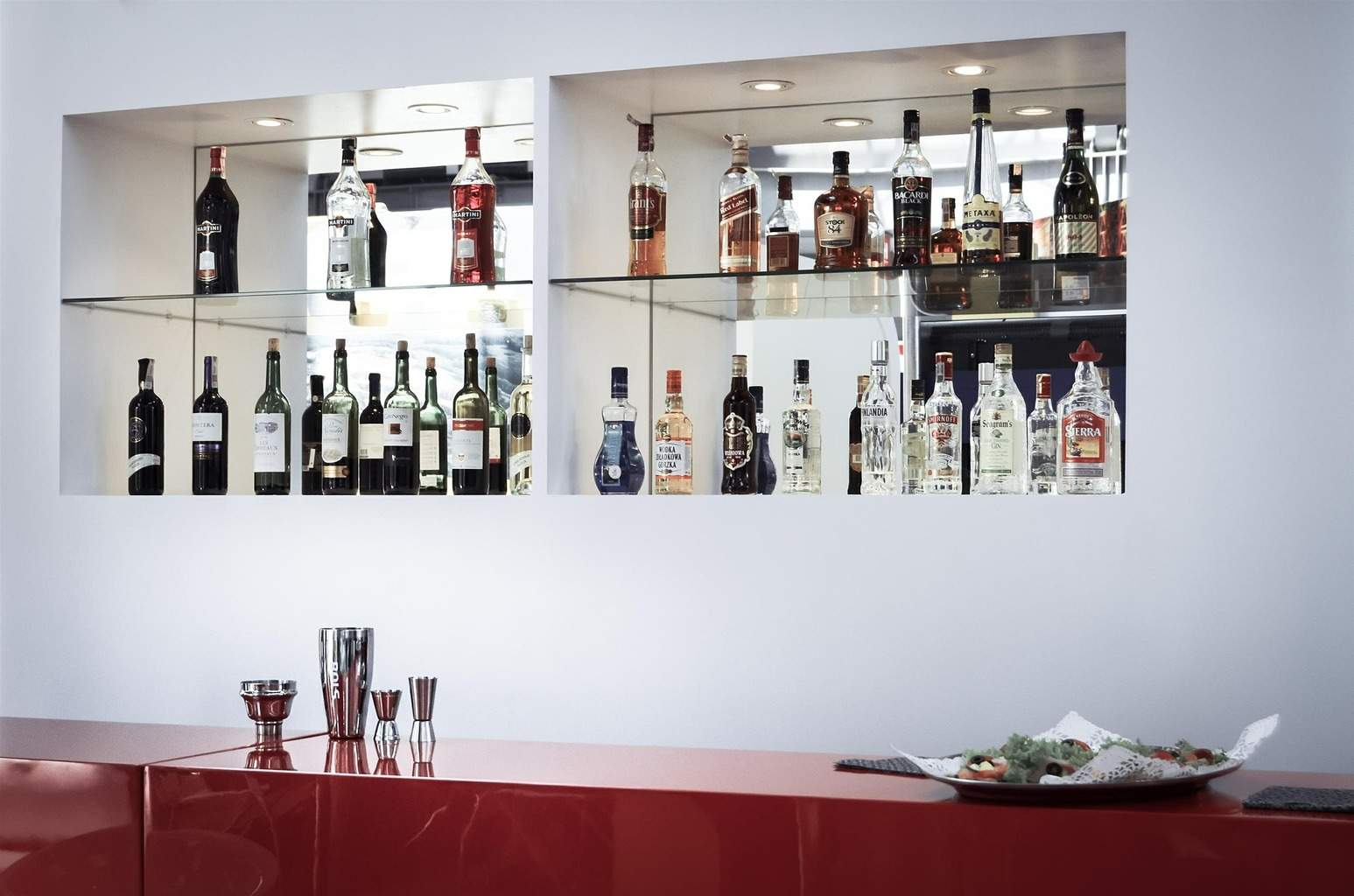 liqueur and spirits bottles neatly arranged on glass shelving behind a bar